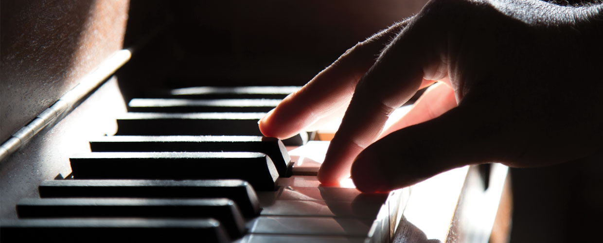 Fingers playing keys on a piano in a beam of sunlight