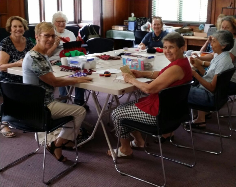 A group of ladies sitting around a table with crafting materials