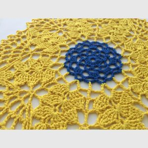 Close up of hand crocheted doily in yellow and blue