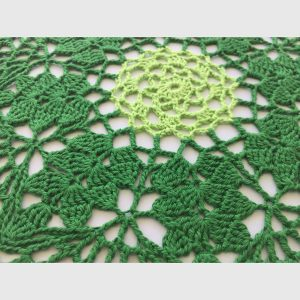 Close up of hand crocheted doily in light and dark green
